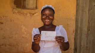 Faith holding up letter from sponsor sister. Photo: Monilekan