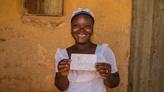 Faith Mathew holding a letter from her sponsored sister