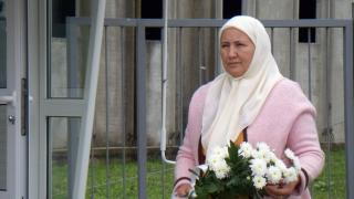 Fazila takes flowers from her shop to lay at her husband