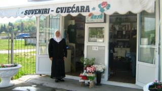 Fazila standing outside her flower shop at the Srebrenica-Potocari Memorial Centre