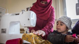 Raja Jidan Ali practices sewing as her daughter Tarq looks on. Photo: Emily Kinsey
