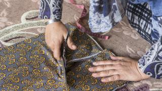 Woman cutting fabric to sew clothes. Photo: Alison Baskerville