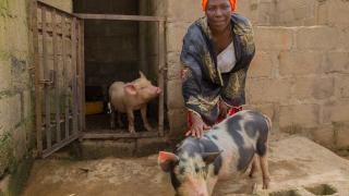 Nanbam with her pigs she purchased using her stipend. Photo: Monilekan