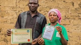 A couple from Nigeria present their Women for Women International graduation certificates for both the Men