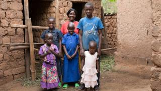 Grace stands with her children outside of their home. Photo: Hazel Thompson