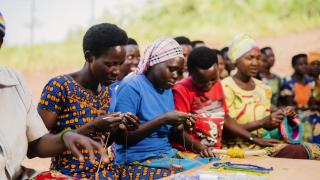 Women learning beading and basketry through Women for Women International