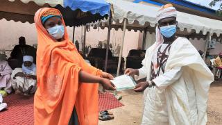 A new graduate receives her certificate at a COVID compliant graduation ceremony in northern Nigeria. Photo: Women for Women International