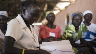 Awate, who was displaced by conflict in South Sudan, takes attendance at a Women for Women International meeting. Photo: Charles Atiki Lomodong