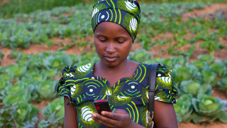 A programme graduate using mobile money to pay her bills