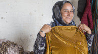 Shireen holding up a dress she made using the skills she learnt during the Stronger Women, Stronger Nations programme. Photo: Alison Baskerville.