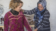 Shireen taking measurements for a traditional Kurdish dress using her daughter-in-law as a model. Photo: Alison Baskerville.