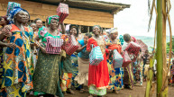 Women show off the baskets they made in vocational training
